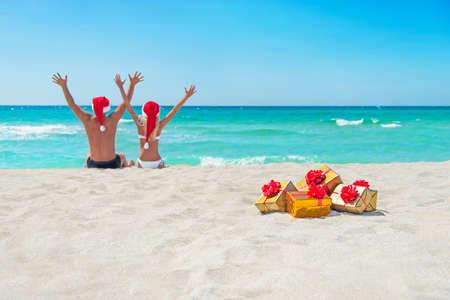 산타 모자에서 행복한 커플 크리스마스 바다 황금 해변 포장 황금 선물