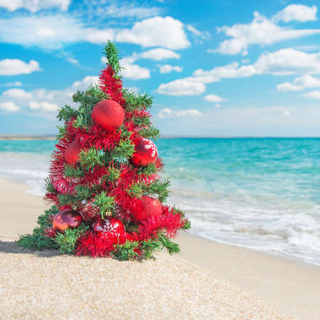 christmas tree with red decorations on the sea beach christmas vacation concept stock photo