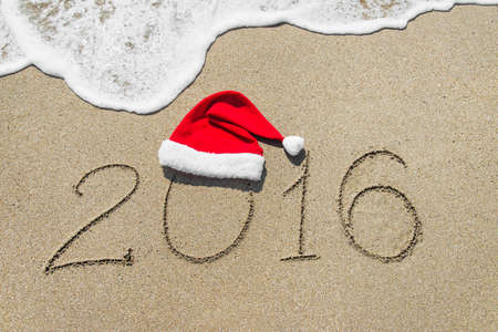 beach happy new year: happy new year 2016 with christmas hat on sandy beach with wave - holiday concept