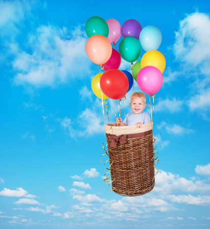 varicoloured: Year-old child flying in blue sky in basket with varicoloured balloons