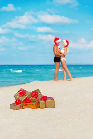 hugging lovers couple in santa hats at sea sandy beach with christmas packed  golden gifts photo