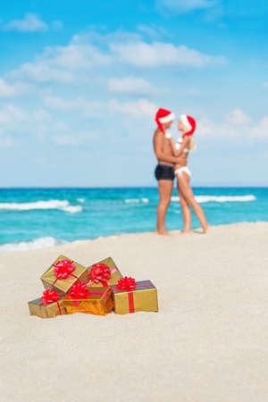 Kissing couple in santa hats at sea sand beach with christmas packed  golden gifts photo