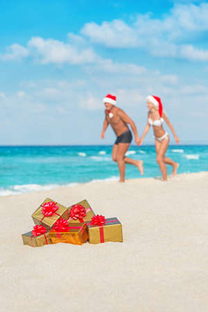 Running couple in santa hats at sea sand beach with christmas packed  golden gifts photo