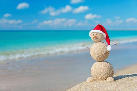 해변 라운지에서 빨간 산타 모자 일광욕에 모래 눈사람. 연말과 크리스마스 카드를위한 휴일 개념.