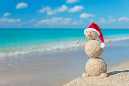 Sandy snowman in red santa hat sunbathing in beach lounge. Holiday concept for New Years and Christmas Cards.