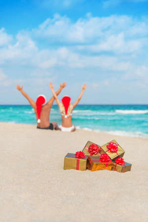 happy couple in santa hats hands up at sea beach with christmas packed  golden gifts photo