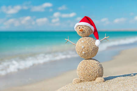 beach happy new year: Smiley sandy snowman in santa hat. Holiday concept for New Years and Christmas Cards. Stock Photo