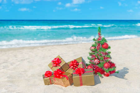 Christmas tree and golden gift with big red bow on the sea sandy beach. Christmas vacation concept.