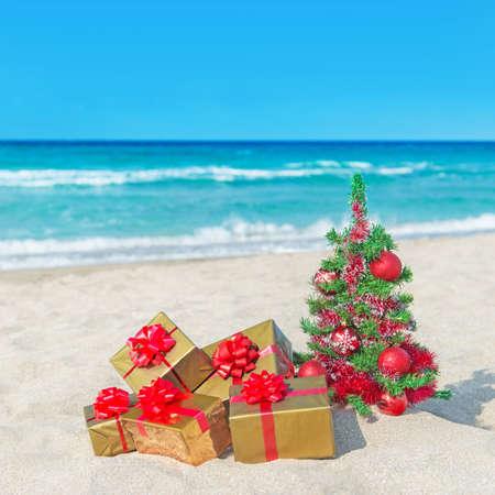 크리스마스 트리 및 바다 모래 해변에 큰 붉은 나비 황금 선물 상자. 크리스마스 휴가 개념. 스톡 콘텐츠