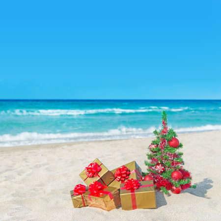 Christmas tree and golden gift boxes with big red bow on the sea sandy beach. Christmas vacation concept.