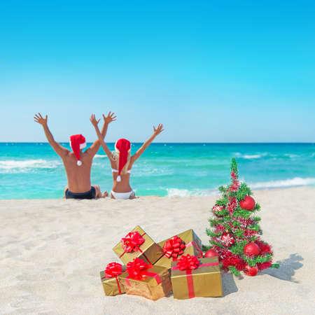 크리스마스 트리와 황금 선물 상자와 함께 바다 해변에서 산타 모자를 손에 행복한 커플까지 스톡 콘텐츠