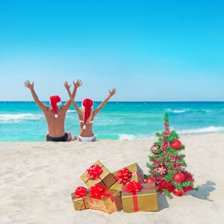 happy couple in santa hats hands up at sea beach with christmas tree and golden gift boxes photo