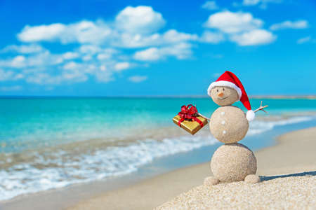 황금 선물과 크리스마스 모자 해변에서 웃는 모래 눈사람. 새로운 년 카드에 대한 휴가 개념. 스톡 콘텐츠 - 24917130
