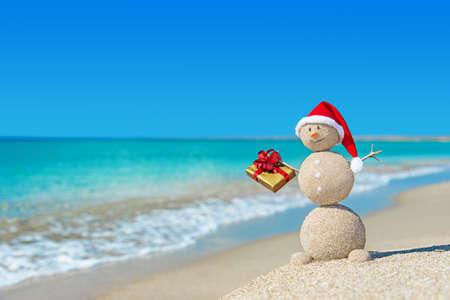 bonhomme de neige: Bonhomme de sable souriant à la plage dans le chapeau de Noël avec un cadeau en or. concept de vacances du Nouvel An cartes.