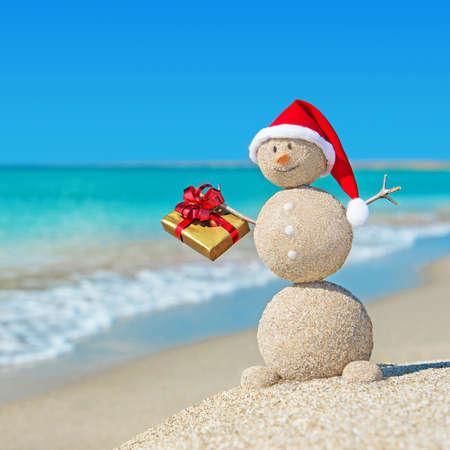 황금 선물과 크리스마스 모자 해변에서 웃는 모래 눈사람. 새로운 년 카드에 대한 휴가 개념.