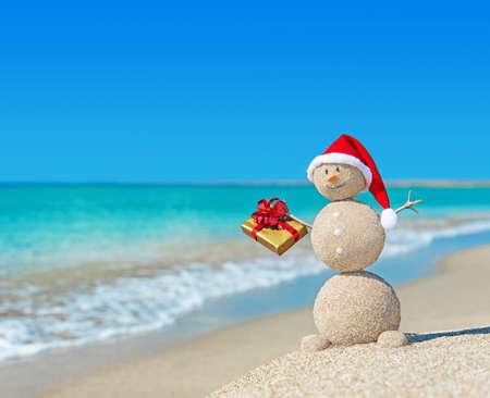 황금 선물 크리스마스 모자 해변에서 웃는 모래 눈사람. 새로운 년 카드 휴일 개념입니다. 스톡 콘텐츠 - 24917133