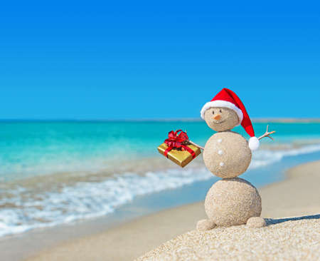 Smiley sandy snowman at beach in christmas hat with golden gift. Holiday concept for New Years Cards.