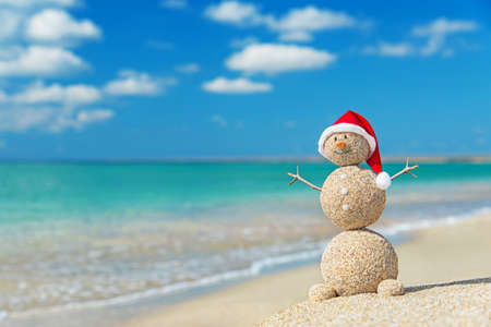 Smiley sandy snowman in santa hat. Holiday concept for New Years and Christmas Cards. Standard-Bild