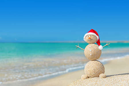 Smiley sandy snowman in santa hat. Holiday concept for New Years and Christmas Cards. Stock Photo