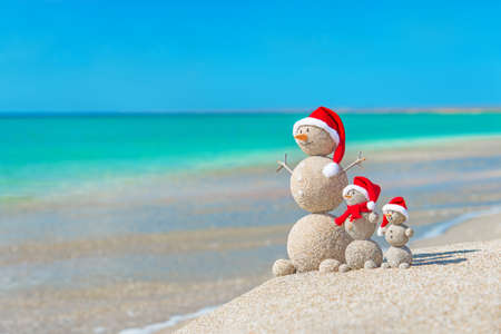 beach happy new year: Snowmans family at sea beach in santa hats. New years and christmas holiday in hot countries concept. Stock Photo