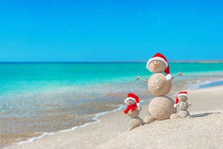 산타 모자에 바다 해변에서 Snowmans 가족입니다. 새로운 년 뜨거운 국가 개념에서 크리스마스 휴가. 스톡 콘텐츠 - 24917140