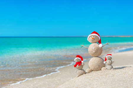 Snowmans family at sea beach in santa hats. New years and christmas holiday in hot countries concept. Banco de Imagens