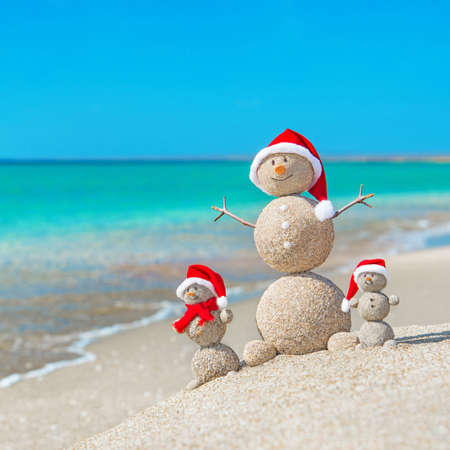 Snowmans family at sea beach in santa hats. New years and christmas holiday in hot countries concept. 스톡 콘텐츠