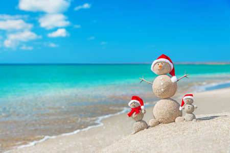 Snowmans family at sea beach in santa hats. New years and christmas holiday in hot countries concept. Standard-Bild