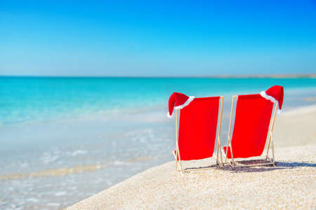 Santa hat on chaise longues at white sand beach against the sea and clear sky - christmas or new year holidays concept Stock Photo