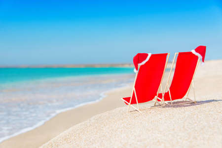 Santa hat on chaise longues at white sand beach against the sea and clear sky - christmas or new year holidays concept photo