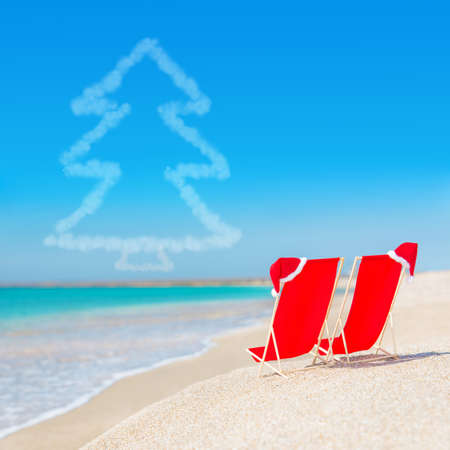 Santa hat on chaise longues at white sand beach against the sea and clear sky with fir tree - christmas or new year holidays concept photo