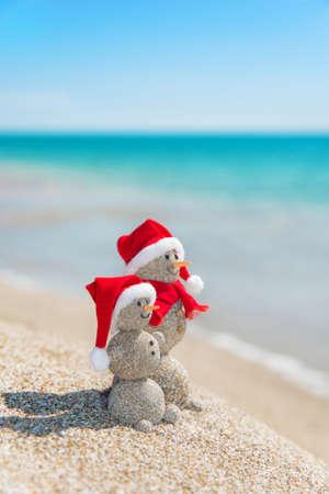 크리스마스 모자에 바다 해변에서 웃는 모래 snowmans 커플. 뜨거운 국가 개념의 새로운 년 휴일. 스톡 콘텐츠