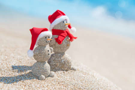 Smiley sandy snowmans couple at sea beach in christmas hat. New years holiday in hot countries concept.