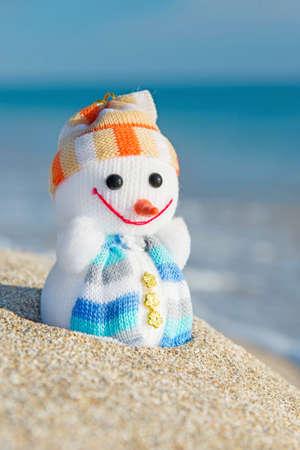 바다 해변에서 웃는 장난감 눈사람. 연말 연시와 크리스마스 카드를위한 휴일 개념. 스톡 콘텐츠