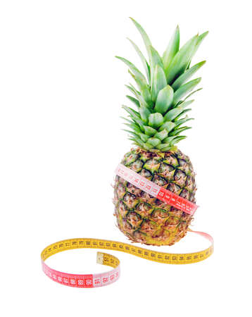 reducing: Pineapple and tape measure isolated on white background as reducing weight concept