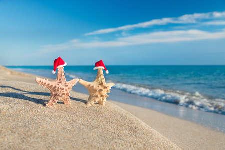 산타 모자에 바다 별 커플 바다 모래 해변에서 산책. 연말 연시와 크리스마스 카드를위한 휴일 개념입니다. 스톡 콘텐츠