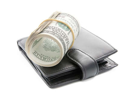 Roll of one hundred dollar bills and leather black wallet isolated a white background photo
