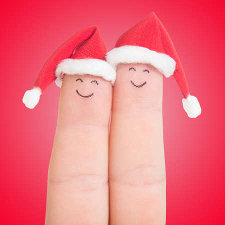 Fingers faces in Santa hats against red background. Happy couple celebrating concept for Christmas day. photo
