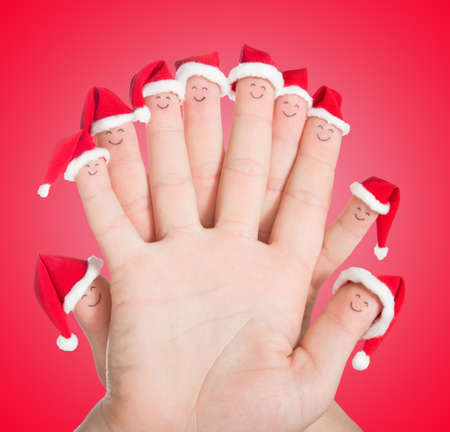 christmas day: Fingers faces in Santa hats against red gradient background. Happy family celebrating concept for Christmas day.