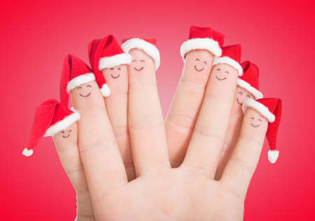 Fingers faces in Santa hats isolated on white background. Happy family celebrating concept for Christmas day. photo