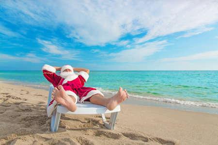 pere noel: bain de soleil du Père Noël de détente dans dormante sur la plage tropicale de sable - concept de Noël
