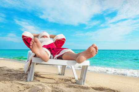 beach happy new year: sunbathing Santa Claus relaxing in bedstone on tropical sandy beach - Christmas concept