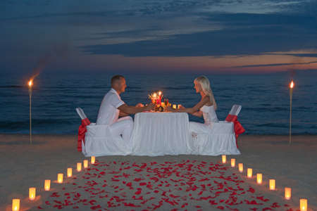 proposal of marriage: Young couple share a romantic dinner with candles, torches and way or rose petals on sea sandy beach against sunset - wedding day, proposal of marriage or honeymoon concept Stock Photo