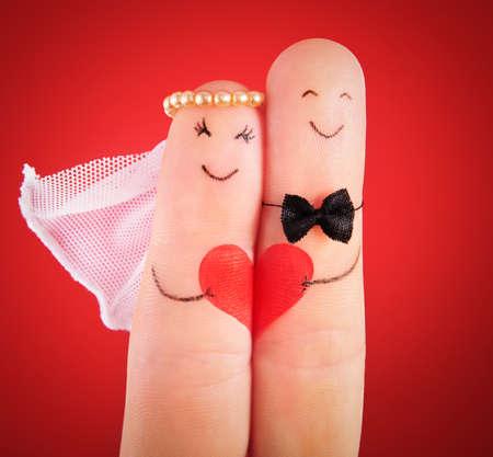 heirat: Hochzeit Konzept - Brautpaar an den Fingern vor rotem Hintergrund gemalt