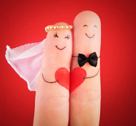 wedding concept - newlyweds painted at fingers against red background Standard-Bild