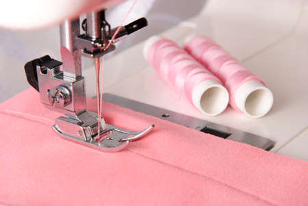 sartorial: sewing process of rosy cloth on the machine and two bobbins background