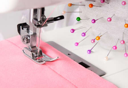 stitchwork: close up of sewing process of on the machine, rosy cloth and manicolored pins Stock Photo