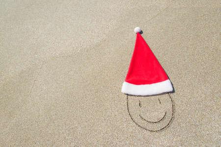 산타 클로스 모자와 파도와 푸른 하늘을 해변에 웃는 얼굴 - 겨울 휴가 개념 스톡 콘텐츠