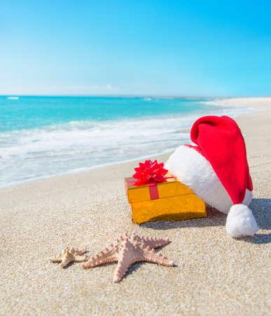 푸른 하늘 바다 별 해변에 산타 클로스 모자 및 골드 크리스마스 선물 상자 스톡 콘텐츠