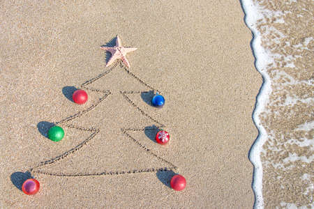 Christmas tree contour with decorations, star and wave on the beach - holiday vacation concept photo